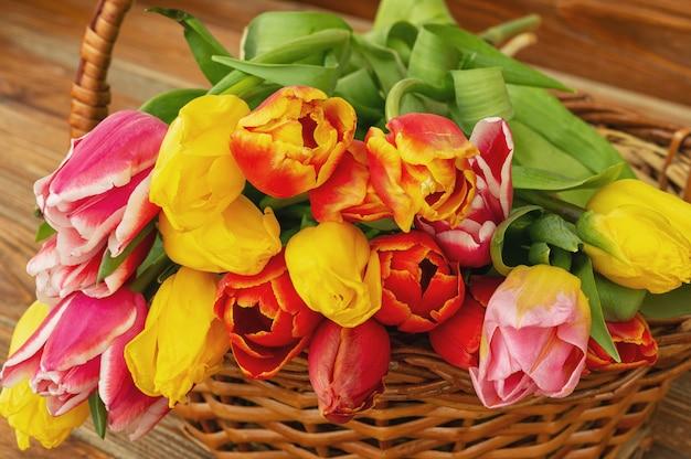 茶色のテーブル、屋外のバスケットにチューリップの花の花束。