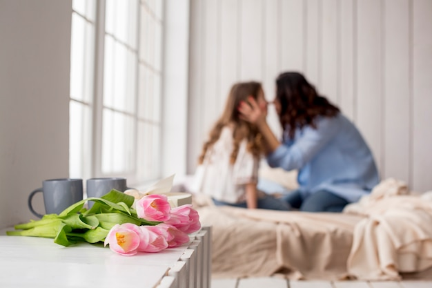 Tulip flowers on table near bed with hugging mother and daughter