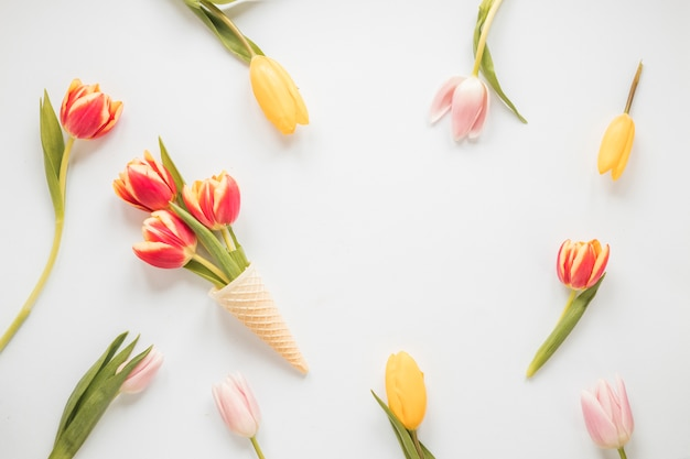 Tulip flowers in waffle cone on table