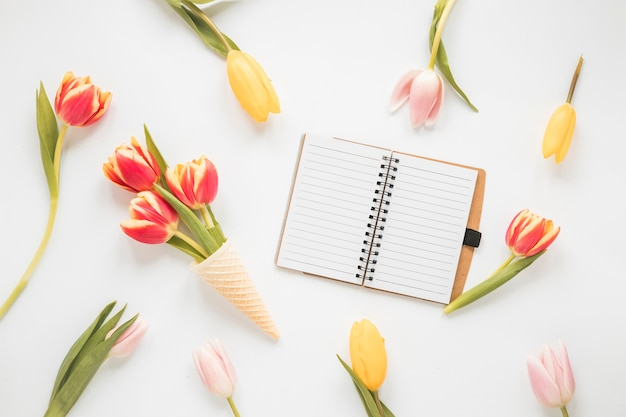 Tulip flowers in waffle cone with blank notebook