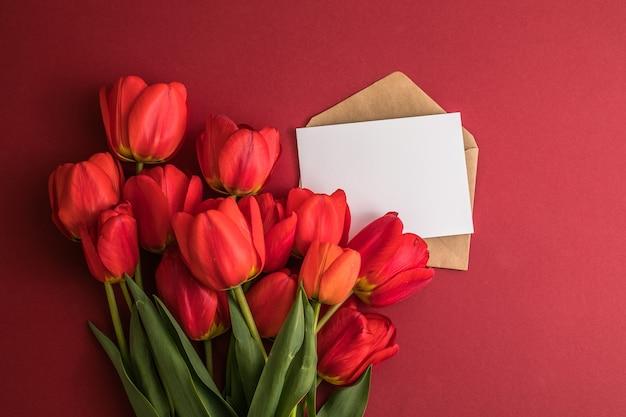 赤い背景の上のカードとチューリップの花