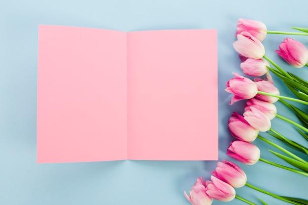 Fiori di tulipano con carta bianca sul tavolo