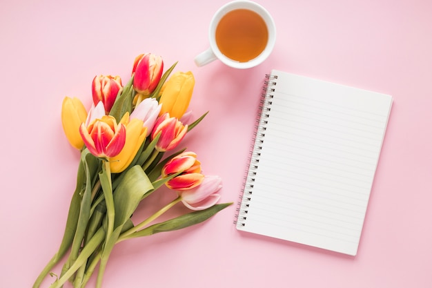 Tulip flowers with notebook and tea cup