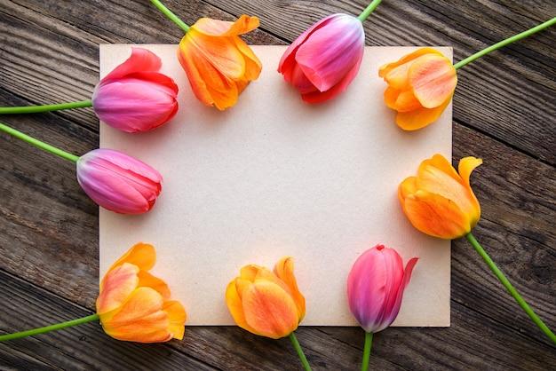 Рамка тюльпан и ретро лист бумаги на деревенском деревянном