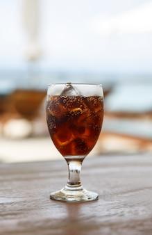 テーブルの上にコーラとチューリップグラス。背景のビーチパラソル。