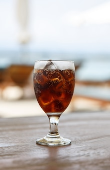 Tulip glass with cola on table. beach umbrellas on the background.