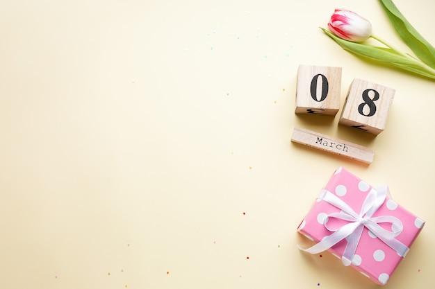 ベージュの背景にギフトと木製のカレンダーが付いたチューリップ、フラットレイ。 3月8日。国際女性の日。