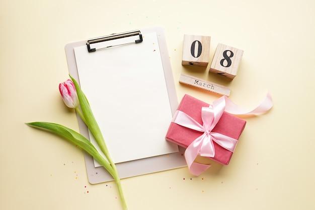 ギフトボックスと木製のカレンダーが付いたチューリップ、3月8日、フラットレイ。女性の日カード。