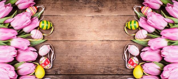 Тюльпаны и яйца граничат на деревянном фоне. пасхальные украшения.