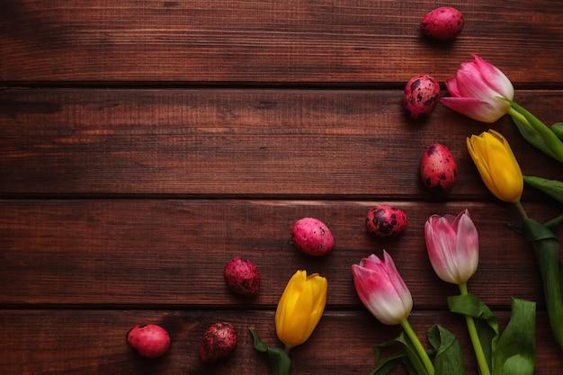 コピースペースと暗い木製の背景にチューリップとピンク色のウズラの卵