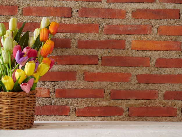Tulips in basket on white table against brick wall