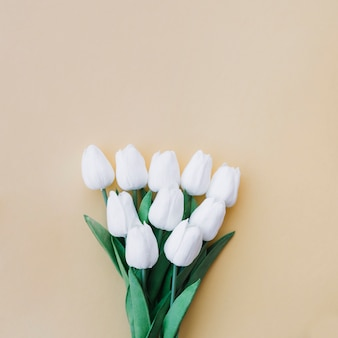 Tulips bouquet on pastel yellow background