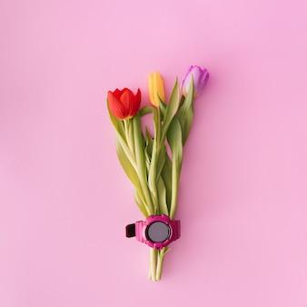 パステルカラーの背景にピンクの時計とチューリップの花束。クリエイティブなフラットレイコピースペース。