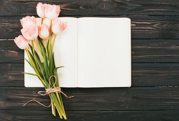 テーブルの上の空白のノートブックとチューリップの花束