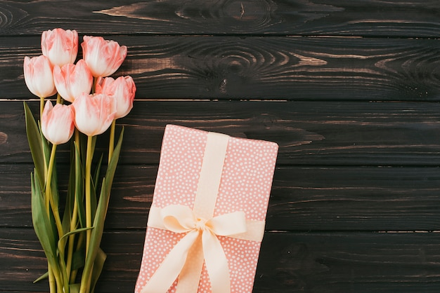 Tulips bouquet with gift box on wooden table