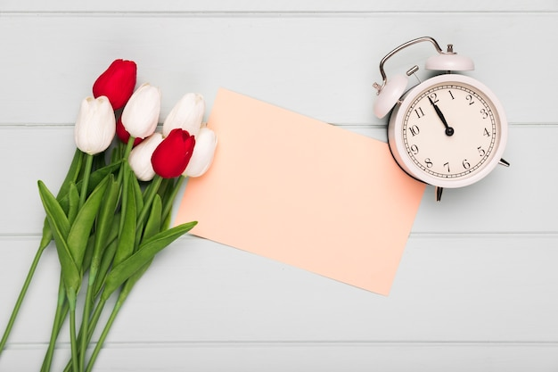 Tulips bouquet with greeting card beside and clock
