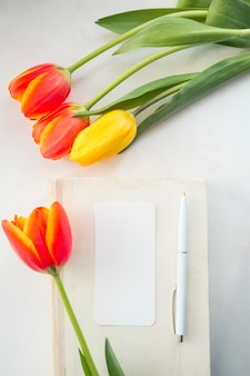 Tulips and envelope with pen placed on desk