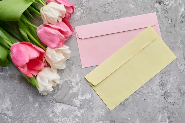 Tulips and envelopes on grunge grey background