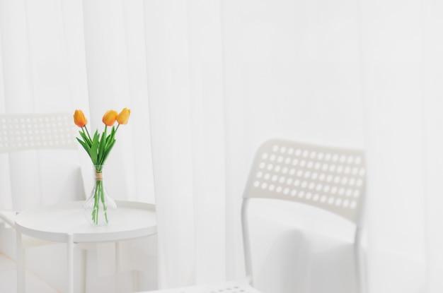 花瓶のチューリップの花は、コピースペースのある白い部屋の背景のテーブルに置かれます。