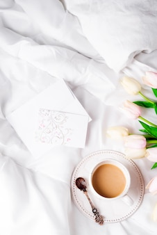 Tulips flower with cup of coffee and post card flat lay morning in bed