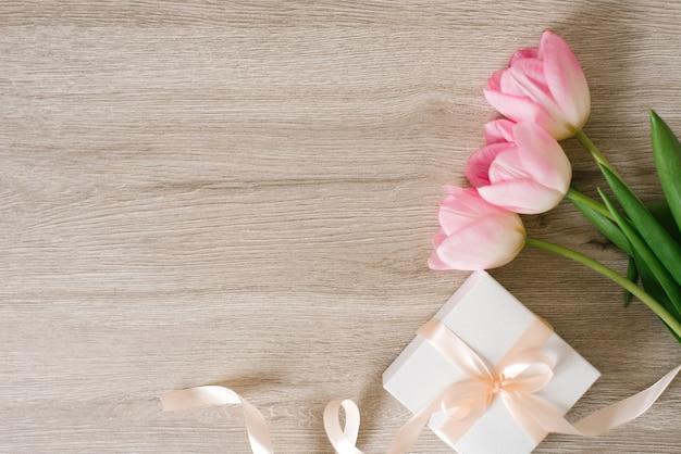木製の背景にチューリップ、ギフトボックス、コーヒー、テキスト用のスペース。フラットレイ。 3月8日、国際女性の日。バレンタイン・デー。