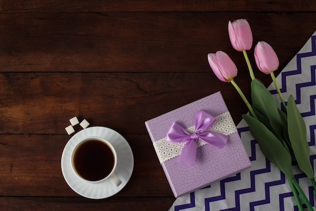 Tulips, gift, cup with coffee on dark wooden surface. flat, top view