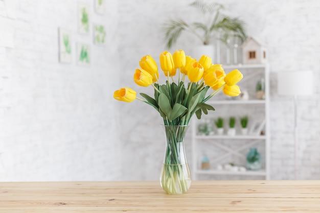 木製のテーブルの上に花瓶のチューリップ。スカンジナビアのインテリア。