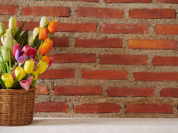Тюльпаны в корзине на белом столе против кирпичной стены