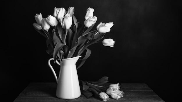 Tulips in a jug on dark background in black and white
