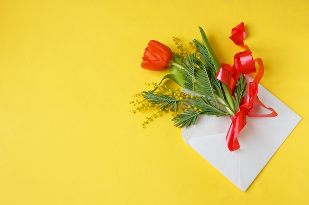 Tulips and mimosa flowers in envelope on yellow