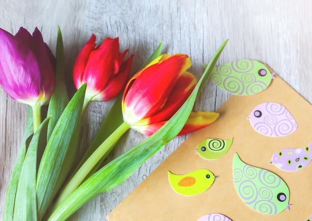 木製トレイの背景にチューリップ。母の日または国際女性デーの招待はがき。クラフト紙の封筒に春の紙のカラフルな鳥。手作りのミニマリストの折り紙。パンチの効いたパステル。 Premium写真