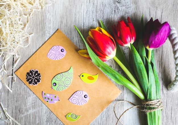 木製トレイの背景にチューリップ。母の日または国際女性デーの招待はがき。クラフト紙の封筒に春の紙のカラフルな鳥。手作りのミニマリストの折り紙。パンチの効いたパステル。