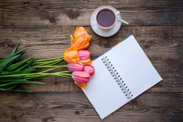 Tulips, open notebook, cup of tea or coffee on wooden surface