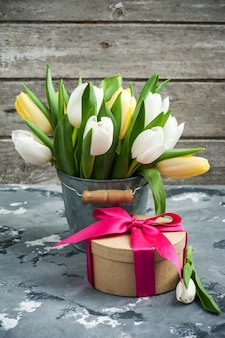 Tulips in tin bucket and a gift package