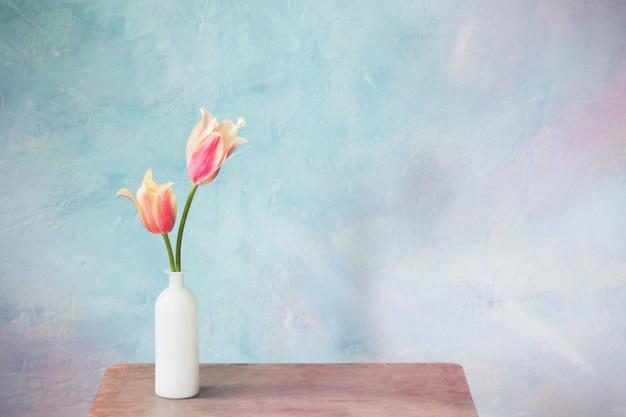 Tulips in vase on blue background
