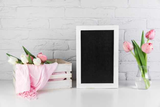 Tulips vase and crate near the blank black white border frame on desk against brick wall