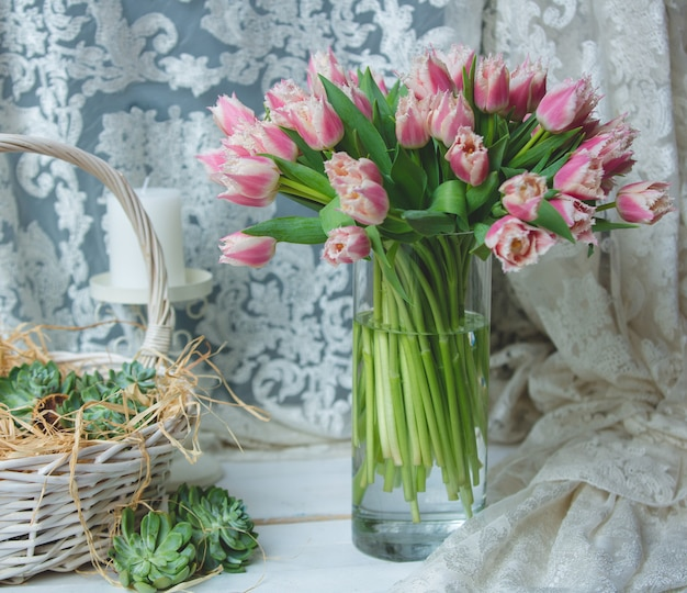 Tulips in a vase and tulle curtain on the font