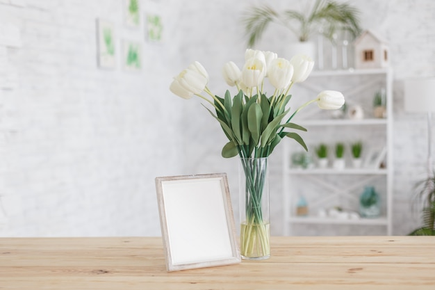 Tulips in a vase on a wooden table. scandinavian interior. mockup.