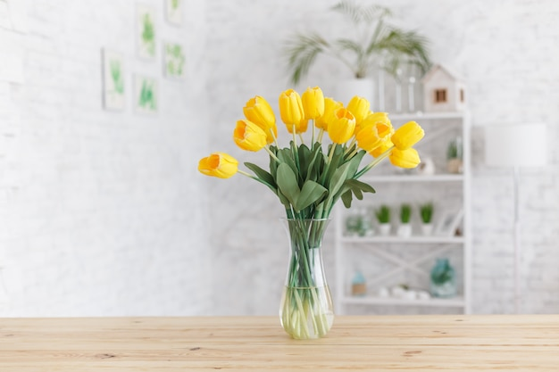 Tulips in a vase on a wooden table. scandinavian interior.