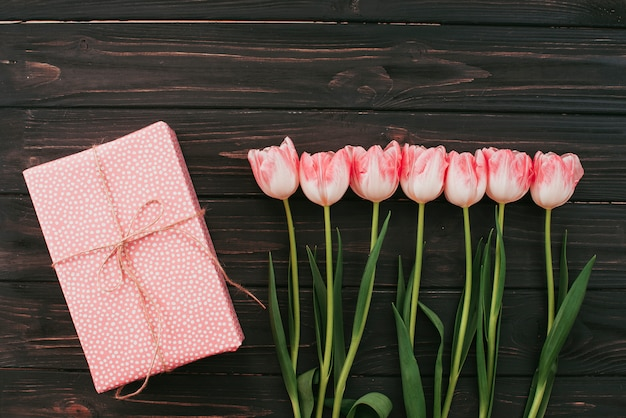 Tulips with gift box on wooden table
