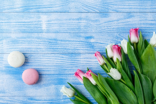 Tulips with macaroons on blue wooden background. rustic tulips.
