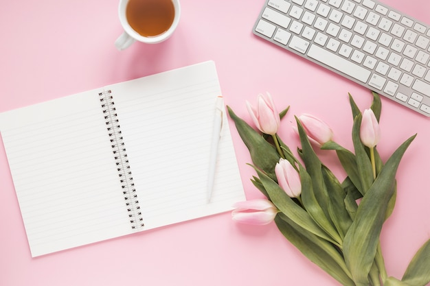 Tulips with notebook, keyboard and tea
