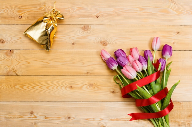 Tulips with red ribbon and gift in gloden bag on natural wooden texture
