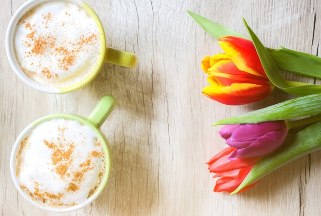 Tulips on wooden background with two cups of coffee. invitation postcard for mother's day or international women's day. punchy pastels. cappuccino with foam cinnamon and flowers.