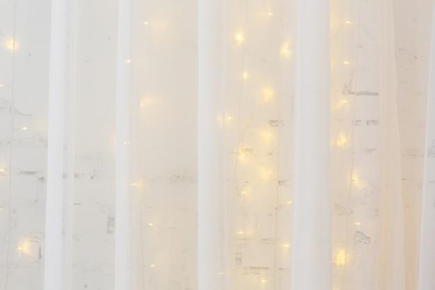 Тюлевые шторы на фоне белой кирпичной стены, украшенной горящей гирляндой