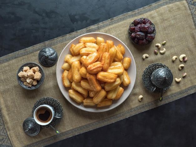 Праздник арабских сладостей ид рамадан. традиционный турецкий десерт тулумба - tulumba tatlisi.