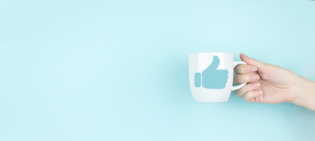 Tumb up concept. girl hand hold morning coffee cup with hand tumb up. copy space. blue background. communication and network concept. like symbol.