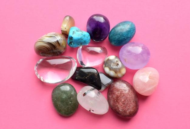 굴러떨어지고 거친 보석과 다양한 색상의 수정. 자수정, 장미 석영, 마노, 인회석, 어벤츄린, 감람석, 분홍색 배경의 청록색.