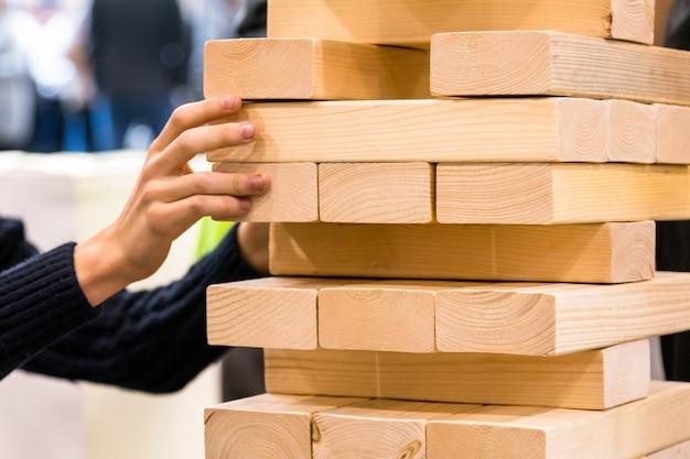 Кувыркаясь в игре с башней, человек тянет деревянную часть деревянной башни.