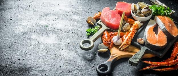 Стейки тунца и лосося на разделочных досках. на черном деревенском